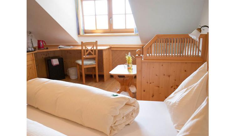 Bett, im Hintergrund hinter einer kleinen Holztrennwand eine Couch, Tisch, seitlich ein Schreibtisch mit Stuhl, im Hintergrund ein Fenster