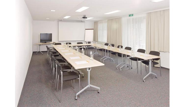 Tisch und Stühle in U-Form aufgestellt, im Hintergrund Fernseher, Flipboard, Leinwand, Beamer an der Decke