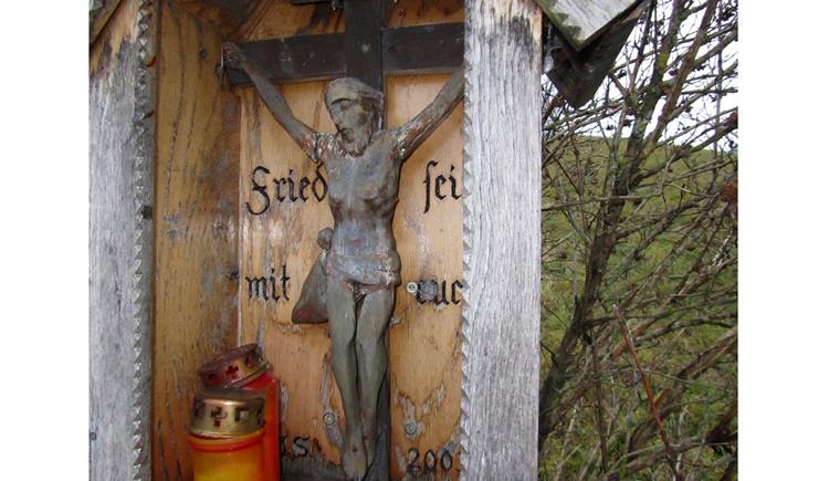 Blick auf ein Kreuz, seitlich Kerzen