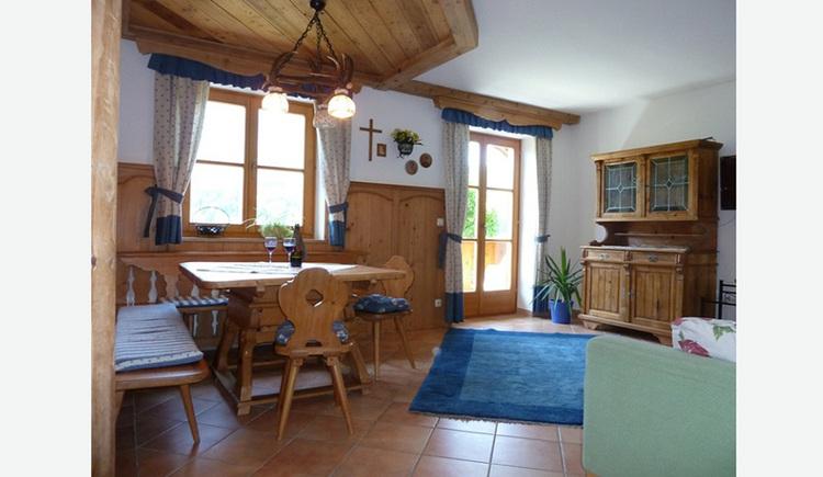 Wohnbereich mit Eckbank, Tisch und Stühle, Teppich, seitlich eine Vollholzkommode mit Glasschrank, im Hintergrund Fenster, offene Balkontür mit Blick auf den Balkon