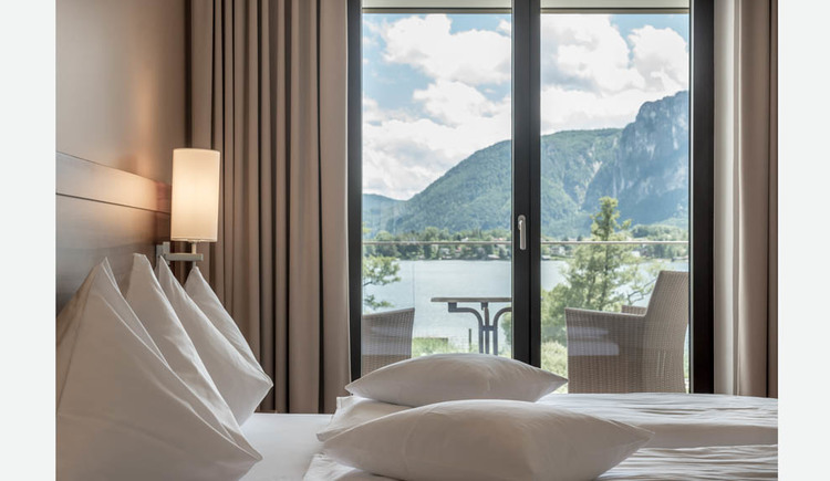 Double bed, lamp, view to the balcony with table and chairs, view of the lake and the mountains