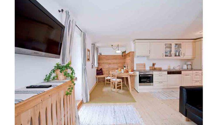 Wohnbereich im Hintergrund der Essbereich mit Tisch und Stühlen, Küche, im Vordergrund eine Couch und Fernseher
