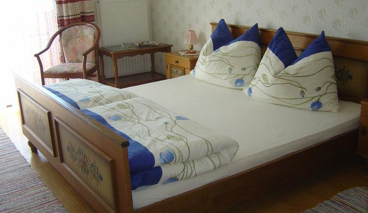 Schlafzimmer mit Doppelbett, Nachtkästchen, Tischlampe, im Hintergrund ein kleiner Tisch, Stuhl, Balkontür