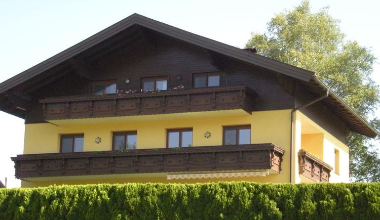 Blick auf das Haus mit Balkon, im Vordergrund eine Hecke