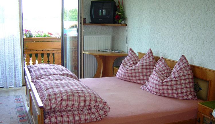 Schlafzimmer mit Doppelbett, Nachtkästchen, kleiner Tisch im Eck drüber ein Fernseher auf einem Eckregal, Blick durch die offene Balkontür auf den Balkon