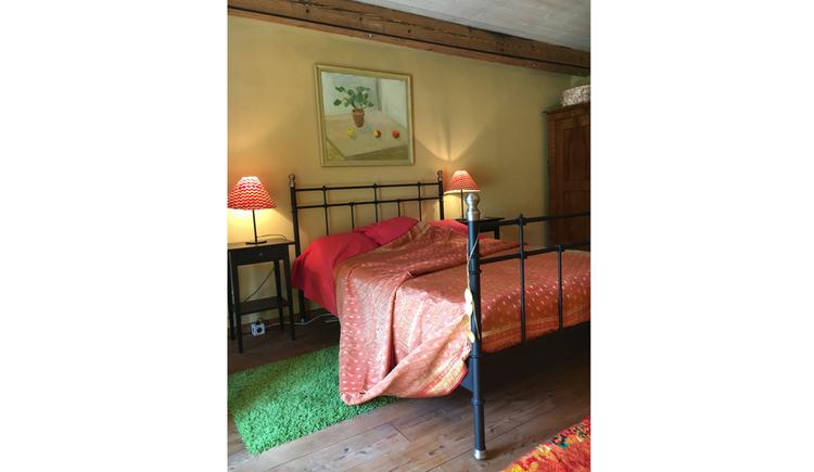 Eisenbett, seitlich davon Nachtkästchen mit Tischlampen, im Hintergrund ein Bild