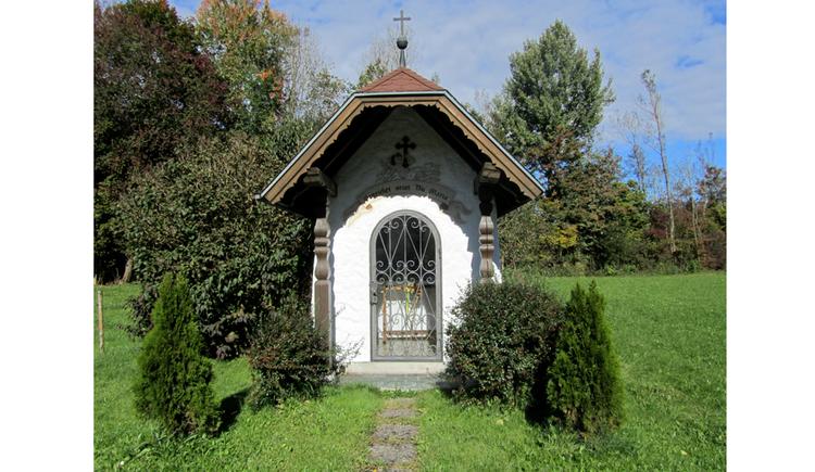 Blick auf die Kapelle, im Vordergrund Sträucher, im Hintergrund Bäume