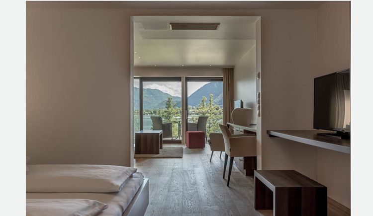 View through the lake suite with double bed, table, chairs, stool, on the terrace chairs and table overlooking the countryside, the lake and the mountains