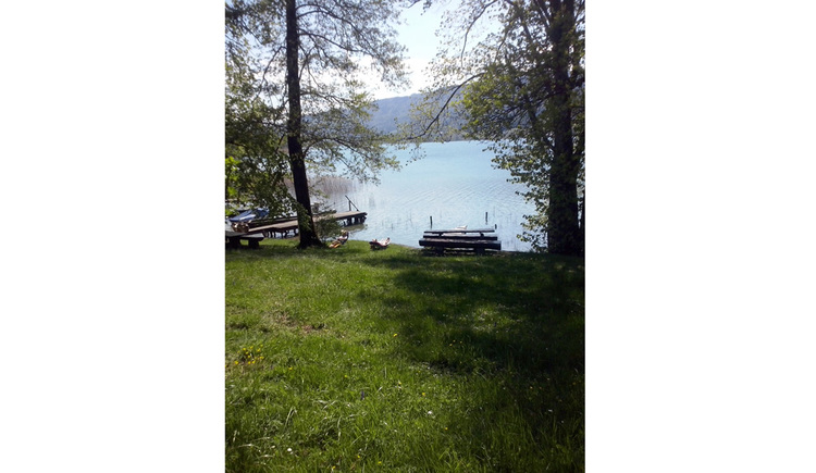 View from the beach to the lake, pier, in the meadow stands a wooden bench and wooden table, in the background the mountains
