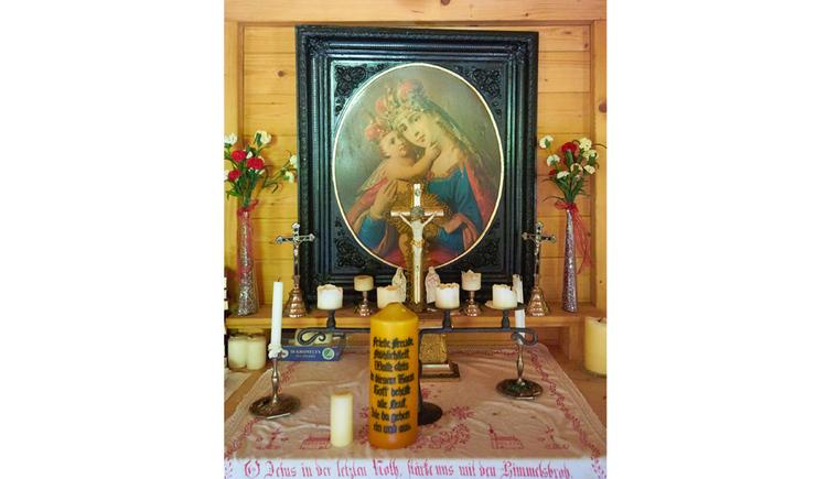 Blick auf den Altar, im Vordergrund Kerzen, im Hintergrund ein Marienbild, Blumen in einer Vase