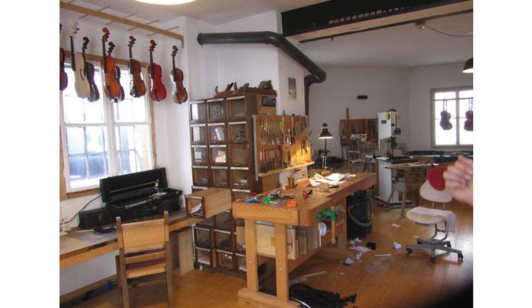 Werkstatt von einem Gegenbauer, seitlich hängen verschiedene Geigen bei einem Fenster