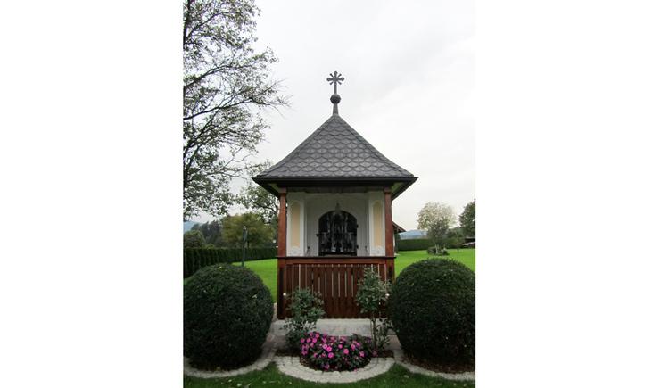 Blick auf die Kapelle, seitlich Sträucher, Blumen
