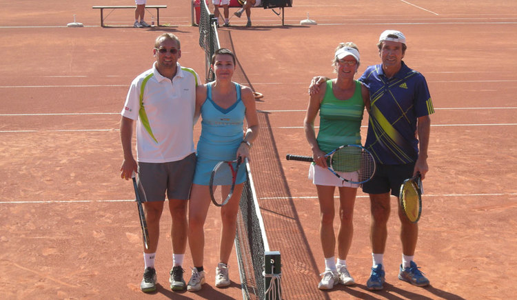 Four people on a tennis court