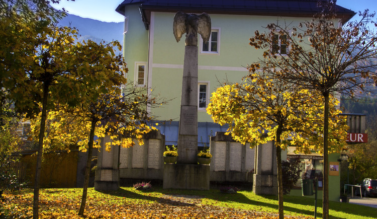 In the middle of the picture the war memorial of Bad Goisern surrounded by trees.
