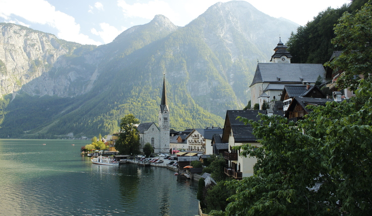 typical view on Hallstatt with the protestant church on the left handside near the lake and the catholic church on the right. Blue sky, just a few clouds and the lake Hallstatt on the left handside.