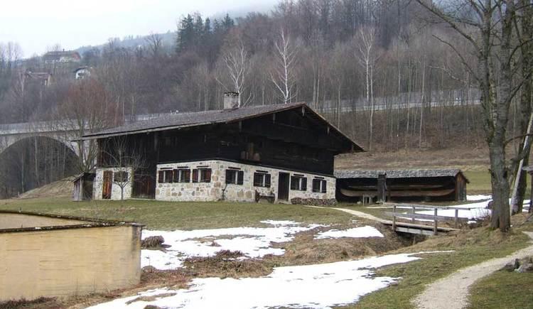 Blick auf ein altes Bauernhaus, im Vordergrund eine Wiese auf der noch etwas Schnee liegt. (© www.mondsee.at)
