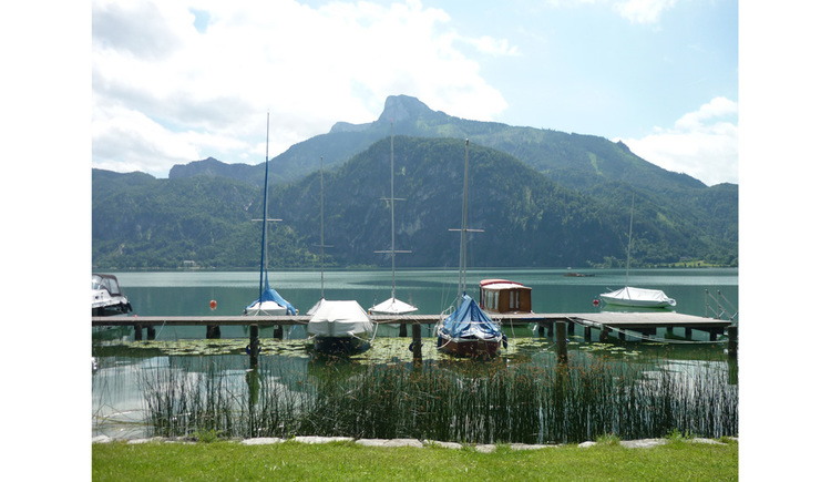 view from the bathingspot onto the lake, footbridge, boots and mountains in the background