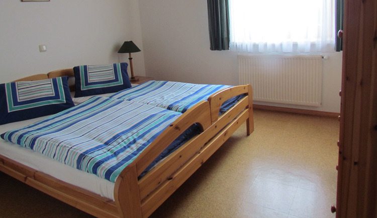 bedroom with double bed, background a window