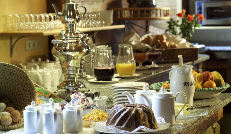 Frühstücksbüffet mit Gugelhupf, Obst, Säften, Marmeladen, Gebäck und Tee bzw. Kaffeekannen
