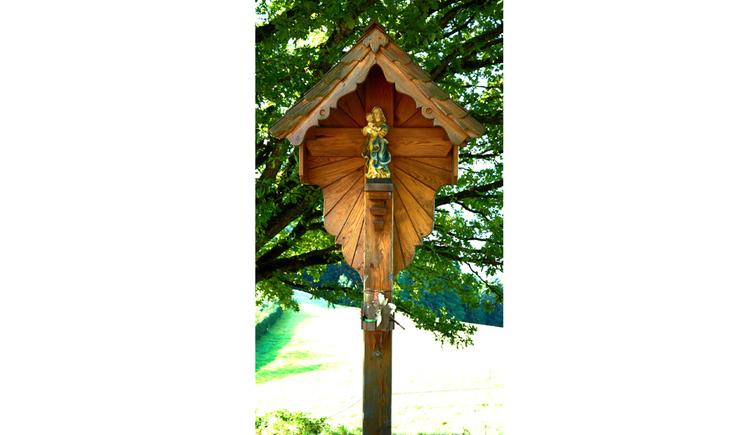 Blick auf den Holzbildstock mit Marienfigur, im Hintergrund ein Baum
