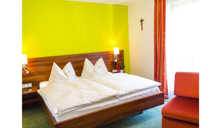 Doppelbett, Lampen, seitlich eine Balkontür, Sessel