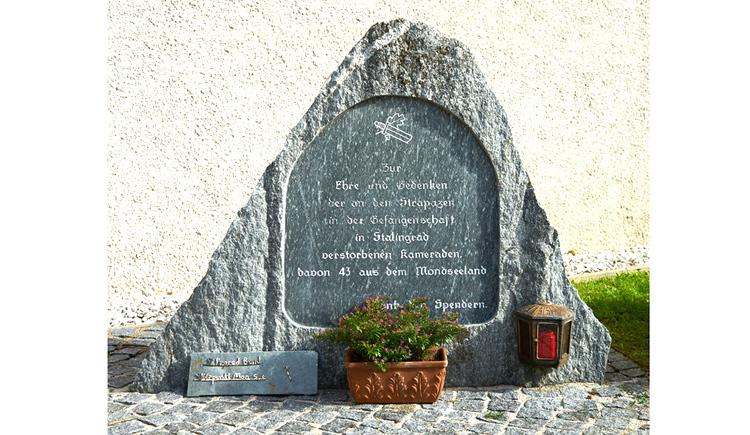 Blick auf den Gedenkstein, im Vordergrund Pflanzen, Kerze