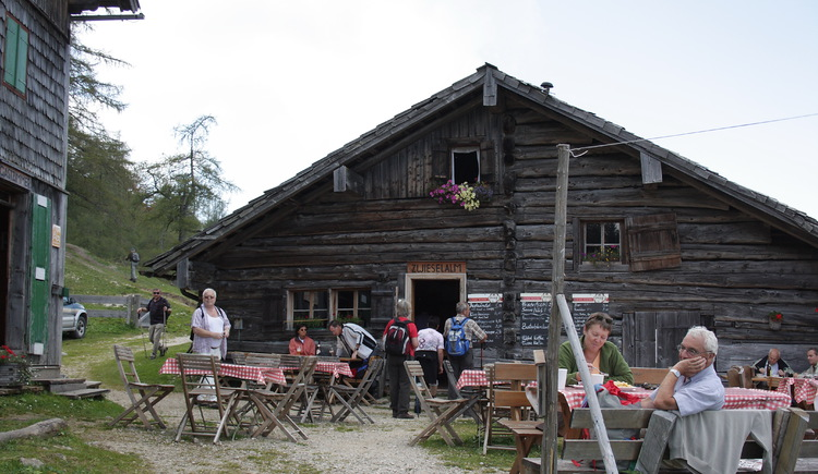 Some hikers enjoy the traditional snack at Zwieselalm hut in summer. (© Elisabeth Grill)