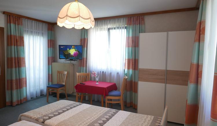Schlafzimmer mit Doppelbett, Tisch mit Stühlen, Fernseher an der Wand, seitlich und im Hintergrund Balkontür und Fenster, Kleiderschrank