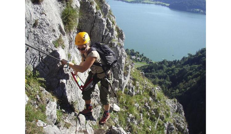Person klettert auf dem Klettersteig, im Hintergrund unten der See