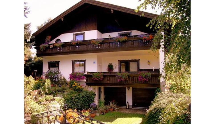 Blick auf das Haus mit Balkon und Blumen, davor der Garten