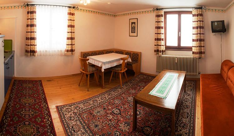 Wohnbereich, seitlich ein kleiner Teil von der Küche, im Hintergrund Fenster, Essbereich mit Eckbank, Tisch und Stühle, Sofa Tisch, im Eck ein Fernseher