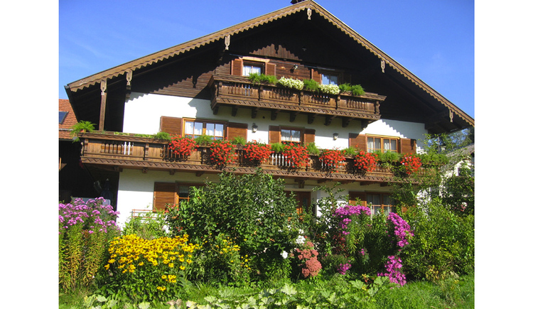 house, balcony with flowers, bush. (© Reichl)