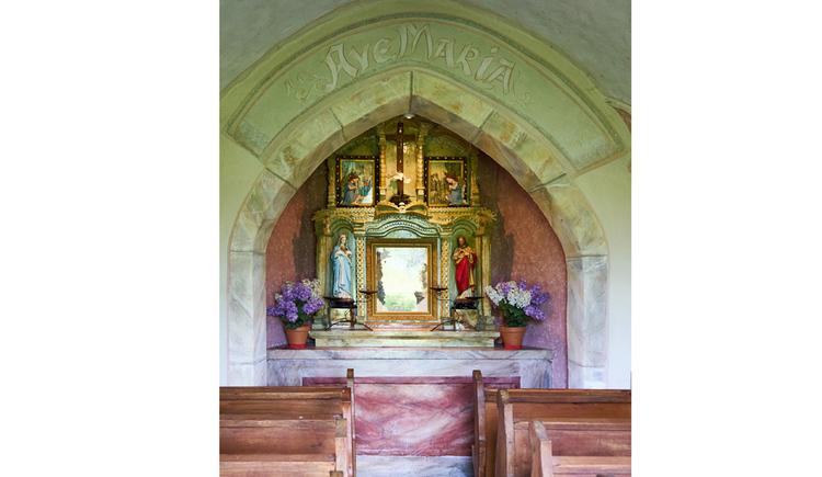 Blick auf den Altar mit Blumen, Heiligenfiguren, Heiligenbilder, seitlich Holzbänke