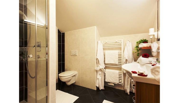 Badezimmer mit Dusche, Toilette, Handtuchtrockner, Waschbecken