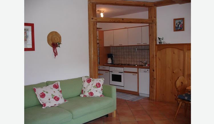 Sofa mit Polster, im Hintergrund die Küche mit Kaffeemaschine, Herd, Spüle, Geschirrspüler, setilich ein Sessel