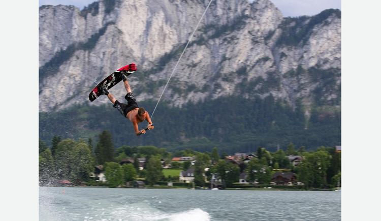 gezogener Wasserskifahrer springt in der Luft auf dem See, im Hintergrund Landschaft und Berge