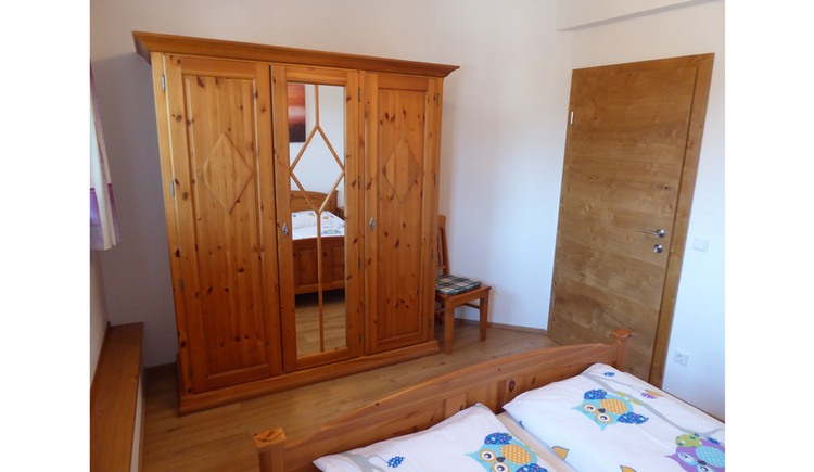 Sleepingroom with a big wardrobe, right a door and in the foreground the doublebed