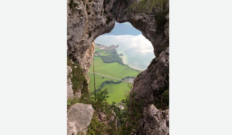 """Blick durch das \""""Drachenloch\"""" Loch im Berg auf den See und die Landschaft"""