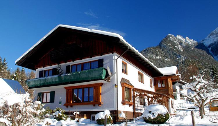 Die Vorderansicht der Ferienwohnung im Winter mit schönem Ausblick auf die umliegende Bergwelt.