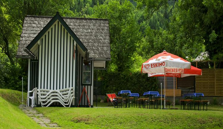 kleines Haus, daneben Bierbänke und Biertische, Sonnenschirme, Wiese, im Hintergrund Bäume