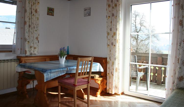 Essbereich, Eckbank, Tisch mit Stuhl, im Hintergrund Blick durch die Balkontür auf den Balkon mit einem Stuhl