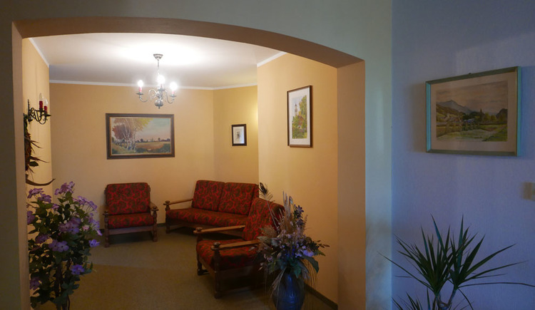 Walkway with flowers, couch with comfortable armchairs, pictures on the wall