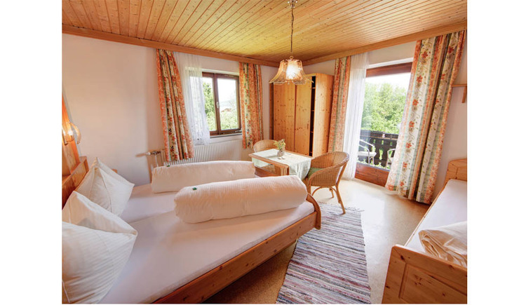 Double bed, single bed, in the background a table with chairs, wardrobe, window, balcony door