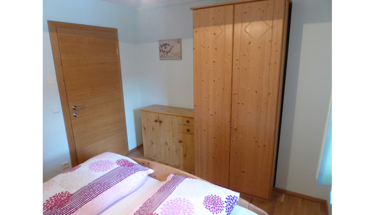 Sleeping room with a doublebed-end infront, in the Background a wardrobe and a dresser, on the rigth side the door