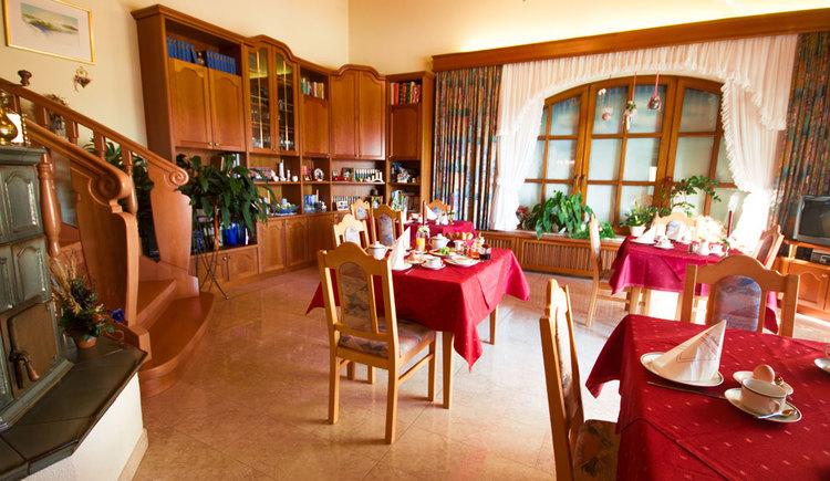 gedeckte Frühstückstische mit Sesseln, im Hintergrund Fensterfront, seitlich Kästen und ein Stiegenaufgang