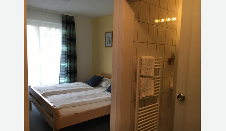 Schlafzimmer mit Doppelbett, im Hintergrund große Balkontür, im Vordergrund Blick durch die offene Schiebetür ins Badezimmer, Handtuchtrockner