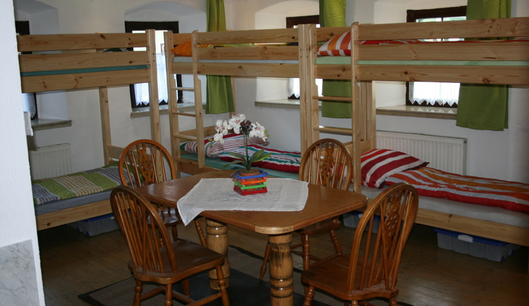 Here you will see the bedroom with the bunk beds and in front view a table with flowers and four chairs.