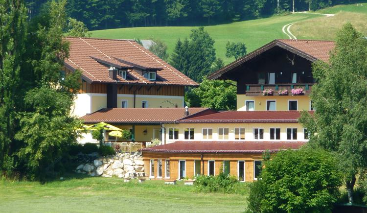 Blick auf den Landgasthof, im Vordergrund Bäume und Wiese. (© Taubenberger)