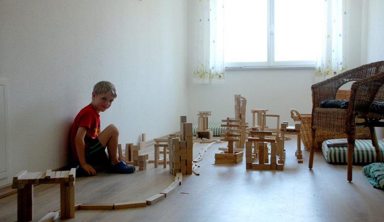 boy plays with wood-play-stones. (© Familienferienhof Stabauer)