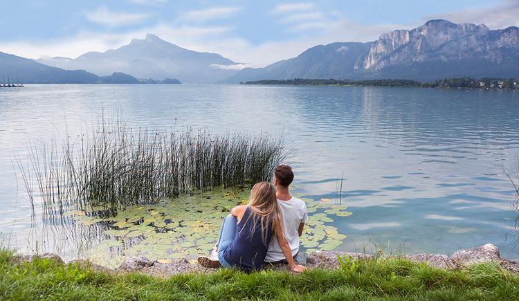 Pärchen sitzt am Ufer, im Hintergrund der See und die Berge. (© Valentin Weinhäupl)